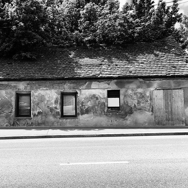 Schief. Also entweder ist das Haus schief oder der Gehsteig. Oder die Straße oder die Ausrichtung der Fenster zueinander - faszinierend finde ich, dass alle erlernte eine unterschiedliche Grundlinie haben. #crooked #vienna #simmering #architecture #instablackandwhite #blackandwhite #oldhouse #crookedstreet #horizon