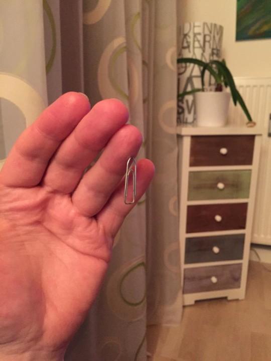 Eine Büroklammer 'schwebt' am Finger mit dem Magneten
