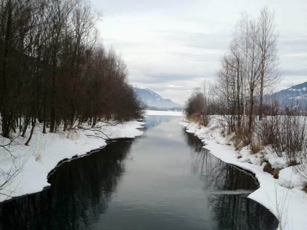 Ein winterlicher Fluss mit leicht vereisten Ufern und Schnee am Flußrand